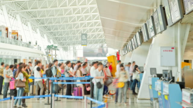 traveler crowd at airport check in counter hall time lapse - airline check in attendant stock videos and b-roll footage