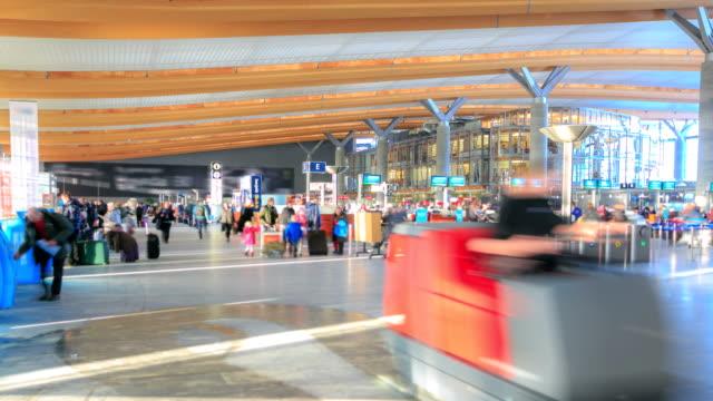vídeos de stock, filmes e b-roll de viajantes s'aglomeram no corredor de balcões do aeroporto para check-in - aeroporto gardermoen de oslo