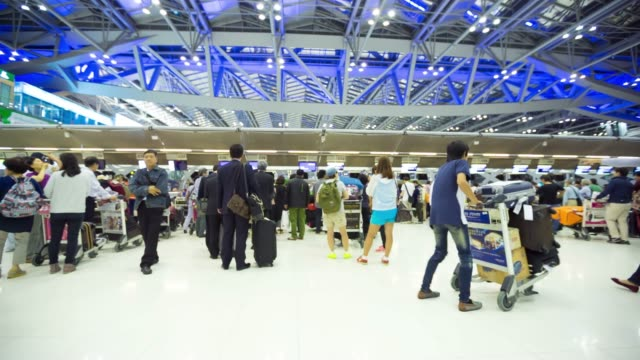 traveler crowd at airport check in counter hall - airline check in attendant stock videos and b-roll footage