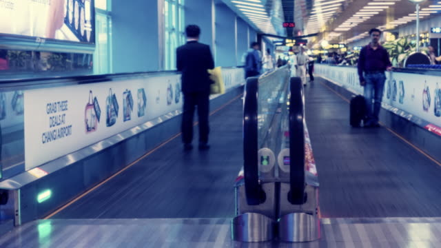 traveler crowd at changi airport escalator, singapore. time lapse - times square causeway bay stock videos & royalty-free footage
