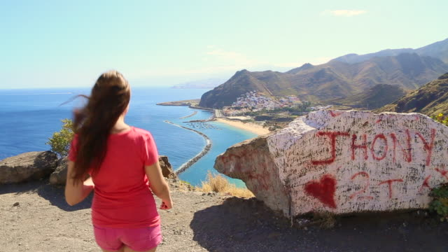 traveler girl contemplating the tenerife island from old ruins viewpoint over the hill during travel vacations to the island with nice views. - braunes haar stock-videos und b-roll-filmmaterial