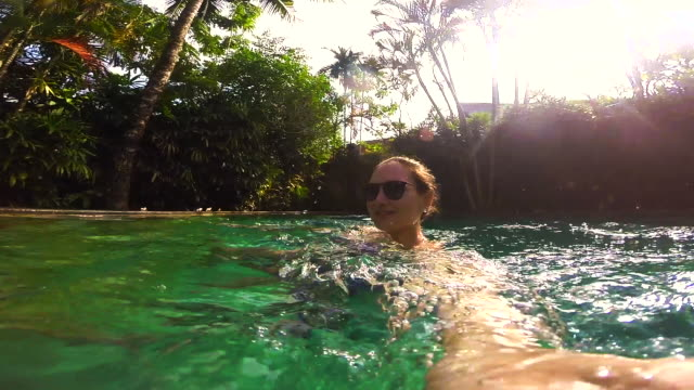 Traveler girl recording himself with video selfie using action cam in swimming pool during travel vacations in the Bali island.