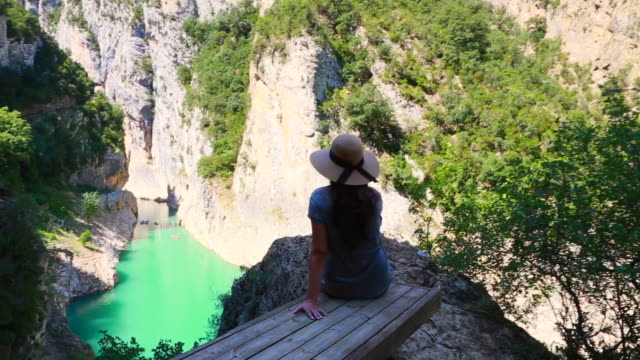 vídeos de stock e filmes b-roll de traveler girl with hat sitting and contemplating the sunning view of the congost de montrebei in the catalan pyrenees during travel vacations in the mountains. - chapéu