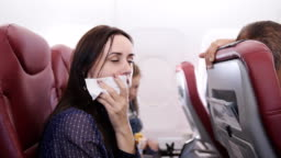Traveler in a flying aircraft has nauseous. Woman on the plane vomited in a paper bag. Nausea passenger in a flying airplane. Turbulence on the plane.