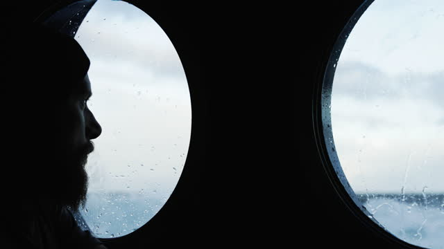 traveler man at the porthole window of a vessel sailing the sea - travel destinations stock videos & royalty-free footage
