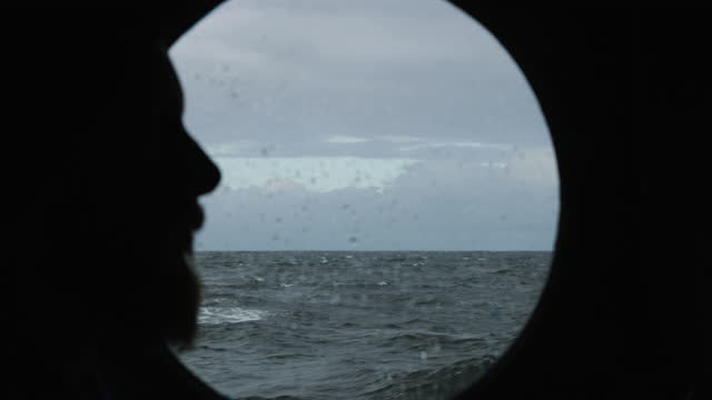 traveler man at the porthole window of a vessel sailing the sea - nostalgia stock videos & royalty-free footage