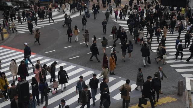 traveler pedestrian crowded walking across the crosswalk at shibuya district area, tokyo, japan. - pedestrian stock videos & royalty-free footage