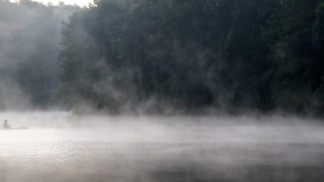 vídeos de stock e filmes b-roll de viajante rafting no lago no nevoeiro - rebento de bambu