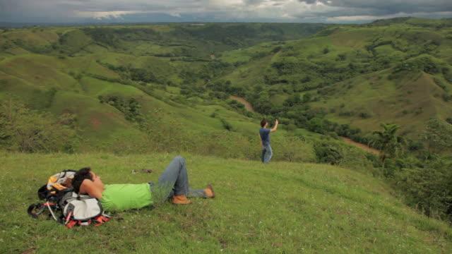 vídeos y material grabado en eventos de stock de ms traveler resting on grass while another taking photo / quimbaya, quindio, colombia  - manos detrás de la cabeza