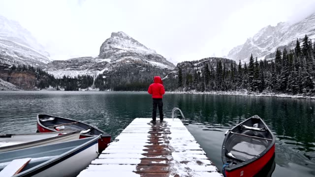 traveler standing on wooden pier with rocky mountains in snowing at lake o'hara, yoho national park - canoe stock videos & royalty-free footage