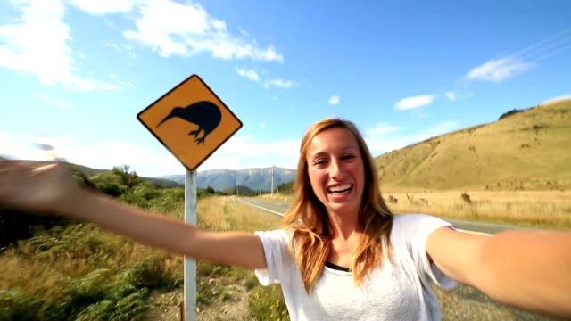 traveler takes selfie portrait on road with kiwi warning sign - road warning sign stock videos & royalty-free footage