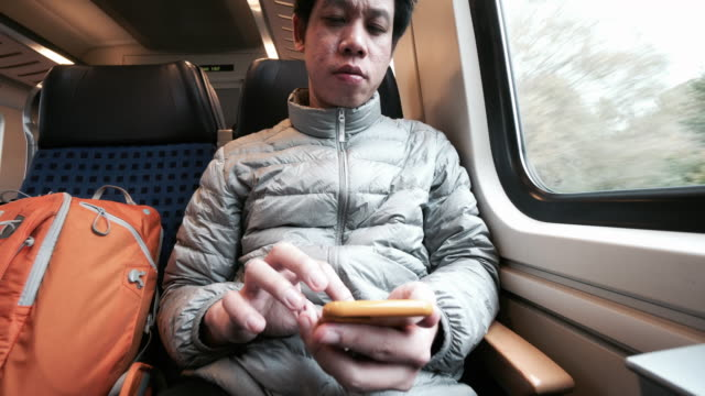 Traveler using mobile phone in the train