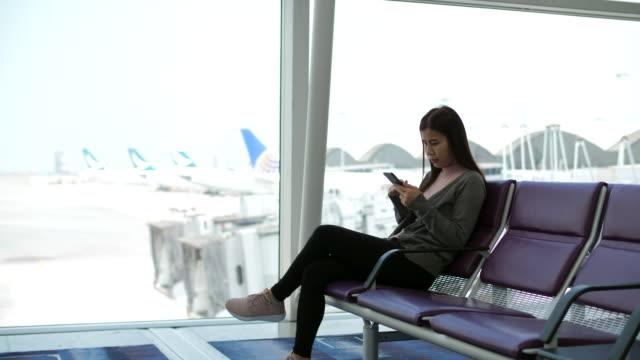 空港ターミナルで待っている旅行者 - 若い女性だけ点の映像素材/bロール