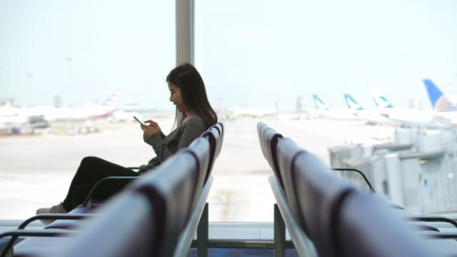 stockvideo's en b-roll-footage met reiziger te wachten in de luchthaventerminal - werkneemster