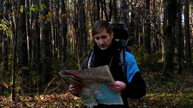 stockvideo's en b-roll-footage met een reiziger loopt in een onbekende bos met een kaart in zijn handen. - bos