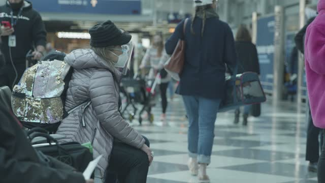 traveler wearing a face shield sits on a bench during the coronavirus pandemic at o'hare international airport on december 18, 2020 in chicago,... - asian and indian ethnicities stock videos & royalty-free footage