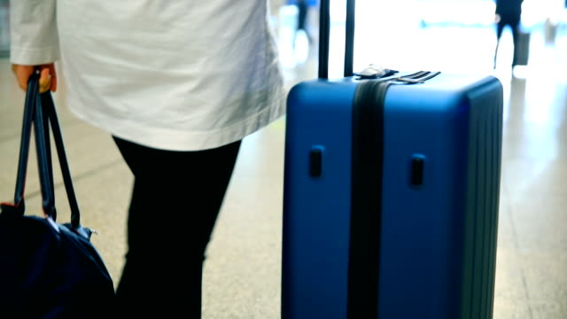 traveler with  luggage walking in airport - reservation stock videos & royalty-free footage