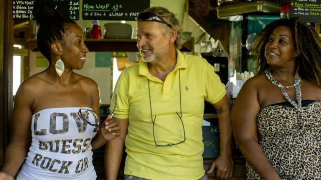 vídeos de stock, filmes e b-roll de a traveler with two young west indian women in a caribbean bar - camisa pólo