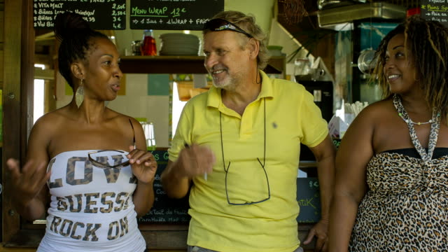 A traveler with two young West Indian women in a Caribbean bar