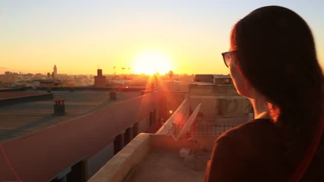 vídeos de stock e filmes b-roll de traveler woman contemplating the stunning sunset over the marrakech medina city from viewpoint terrace during travel vacations in morocco. - retroiluminado