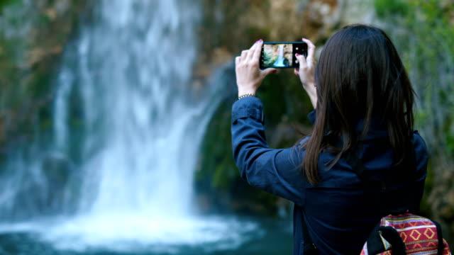 traveler woman taking photo of amazing waterfall - photo messaging stock videos & royalty-free footage