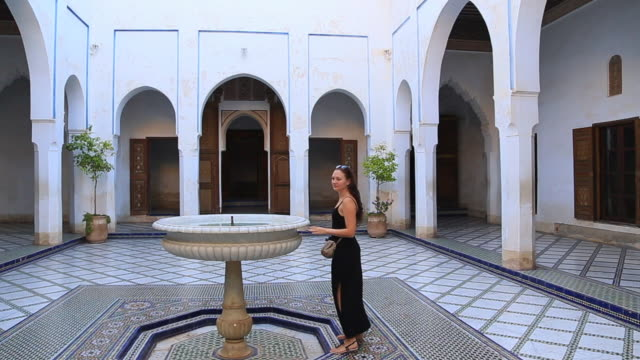 traveler woman visiting beautiful white palace in marrakech city with nice open patio with fountain during travel vacations in morocco. - dress stock videos & royalty-free footage
