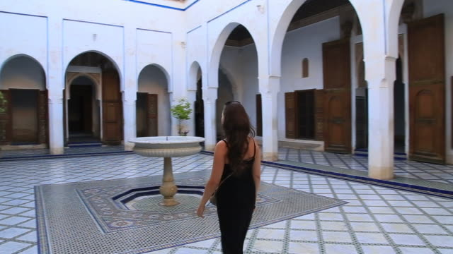 traveler woman visiting beautiful white palace in marrakech city with nice open patio with fountain during travel vacations in morocco. - black dress stock videos & royalty-free footage