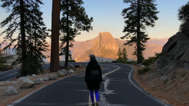 traveler woman walking in the glacier point road with the half dome. - half dome stock videos & royalty-free footage