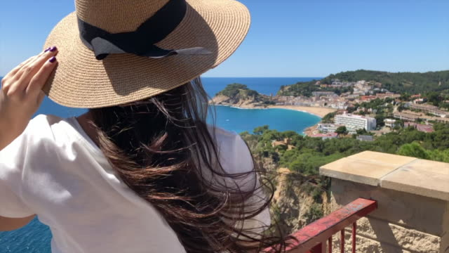 stockvideo's en b-roll-footage met traveler woman with hat in a windy day contemplating the coastline of costa brava. - mar
