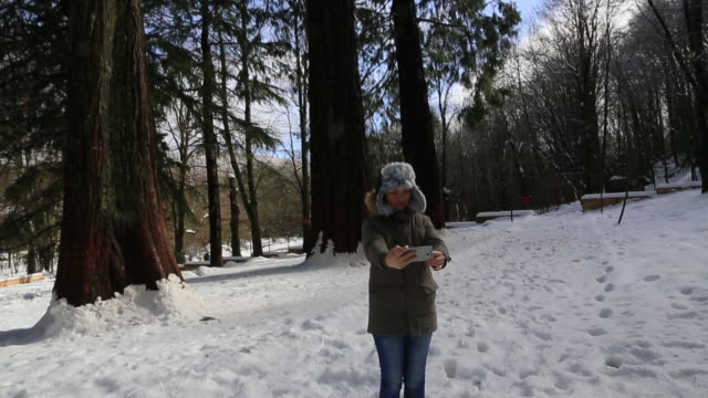Traveler woman with winter hat taking a selfie with smartphone under the tall sequoia trees during day trip in the Montseny nature reserve.