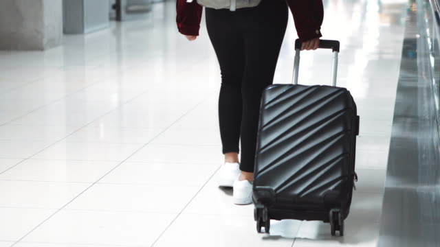 traveler women walking across the airport terminal with suitcase in the airport , travel concept - boarding stock videos & royalty-free footage