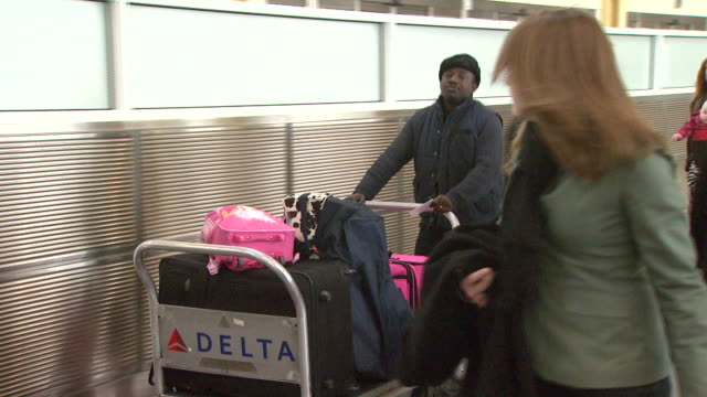 Travelers and staff walking in terminal with baggage at Ronald Reagan Washington National Airport / Arlington Virginia United States