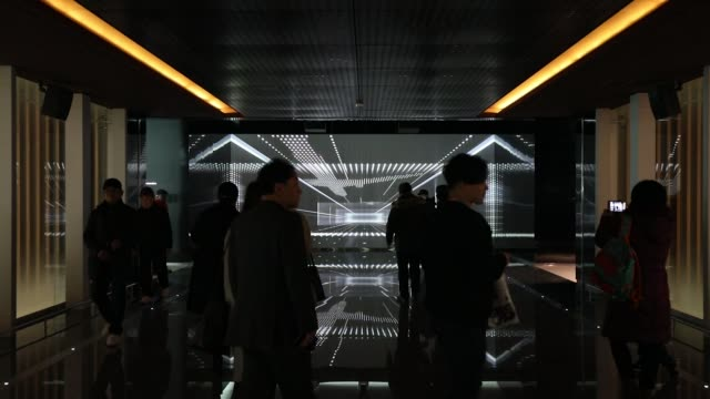 Travelers are silhouetted as they walk through a screen inside the terminal 2 building at Incheon International Airport in Incheon South Korea on...