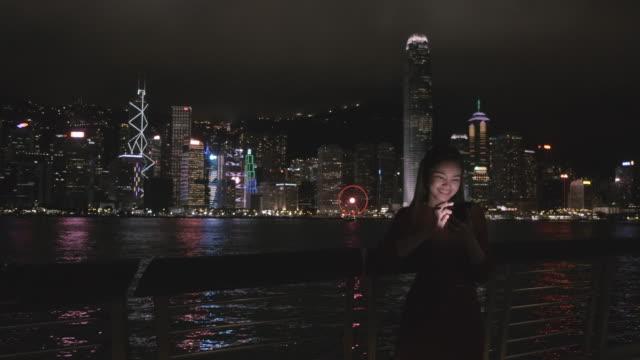 vídeos de stock, filmes e b-roll de os viajantes estão usando telefones celulares para conectar a rede da cidade de hong kong à noite. - trabalhadora de colarinho branco