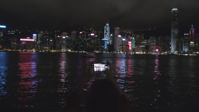 travelers are using mobile phones to take pictures of hong kong city at night. - victoria harbour hong kong stock videos & royalty-free footage