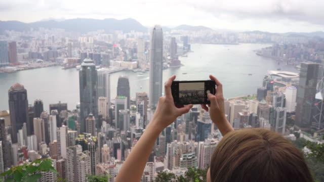 vidéos et rushes de les voyageurs utilisent des téléphones mobiles pour prendre des photos de la ville de hong kong - jour