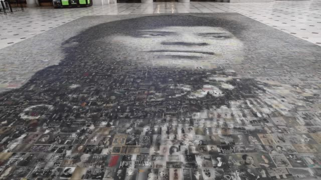 """travelers at union station walk by the the mural, titled """"our story: portraits of change,"""" of civil rights icon ida b. wells. it was designed by... - アメリカ黒人の歴史点の映像素材/bロール"""