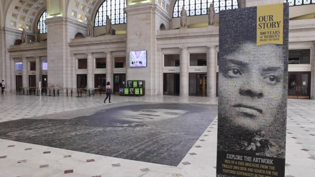 """travelers at union station walk by the the mural, titled """"our story: portraits of change,"""" of civil rights icon ida b. wells. it was designed by... - black history in the us stock videos & royalty-free footage"""