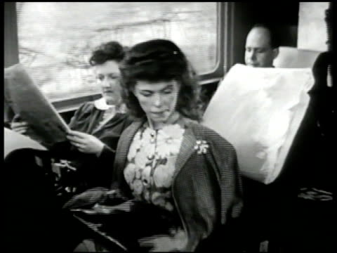 Travelers commuters riding in coach in train MS Woman getting pillow at seat MS Engine man in cab Moving on railroad tracks WS People in lounge car...