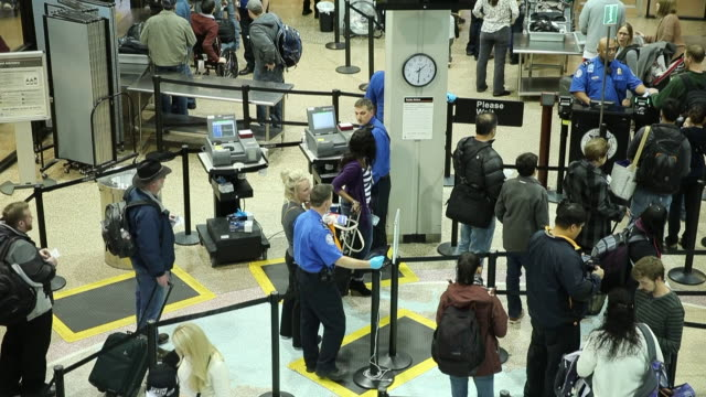 Travelers enter a security check in line inside a terminal at the Salt Lake City International Airport in Salt Lake City Utah TSA employees check IDs...
