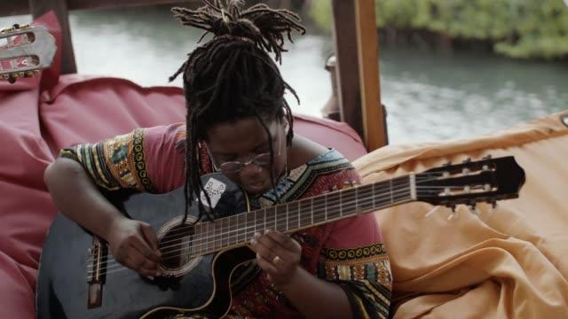 vídeos de stock e filmes b-roll de travelers from diverse backgrounds make music together - territórios ultramarinos franceses