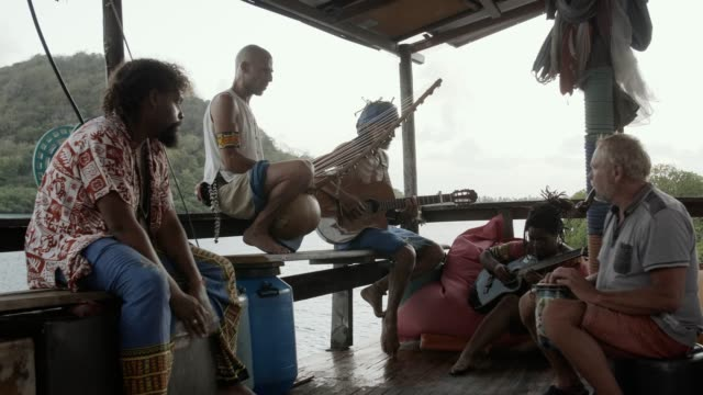 travelers from diverse backgrounds make music together - french overseas territory stock videos & royalty-free footage