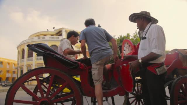 vídeos de stock e filmes b-roll de ms travelers getting up on horse carriage / cartagena, bolivar, colombia    - colômbia