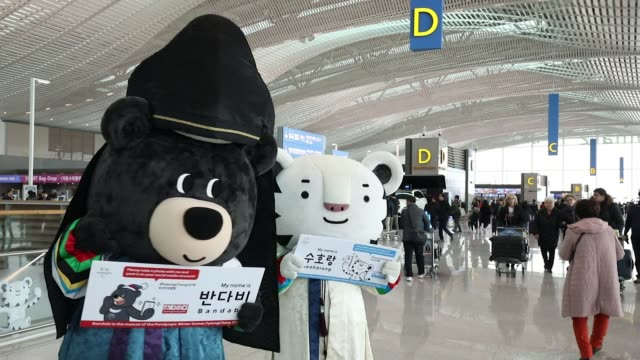 Travelers have their pictures taken with workers dressed as characters of the 2018 PyeongChang Winter Olympic Games mascot Soohorang right and...