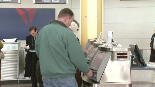 travelers operating automated ticket dispensers at reagan national airport / arlington, virginia, united states - ロナルド レーガン ワシントン国際空港点の映像素材/bロール