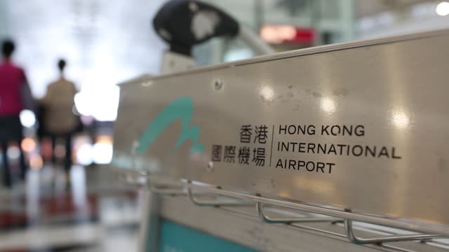 travelers push their luggage on a trolley while walking through hong kong international airport in hong kong china on thursday oct 10 airline... - flugpassagier stock-videos und b-roll-filmmaterial