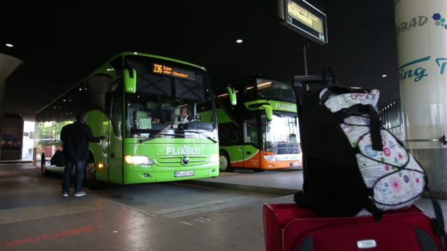 Travelers queue to board a FlixBus passenger bus at Munich central bus station in Munich Germany on Friday April 27 2018