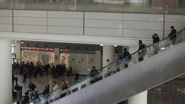 travelers ride escalators in the shanghai hongqiao railway station in shanghai china on monday feb 12 travelers stand at ticketing counters at the... - bahnreisender stock-videos und b-roll-filmmaterial