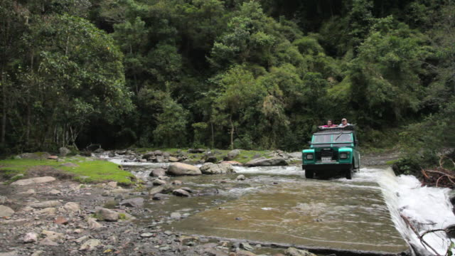 ms travelers riding across river on back of jeep / salento, quindio, colombia   - fahrzeug fahren stock-videos und b-roll-filmmaterial