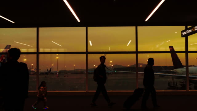 travelers silhouettes at airport - vanishing point stock videos & royalty-free footage